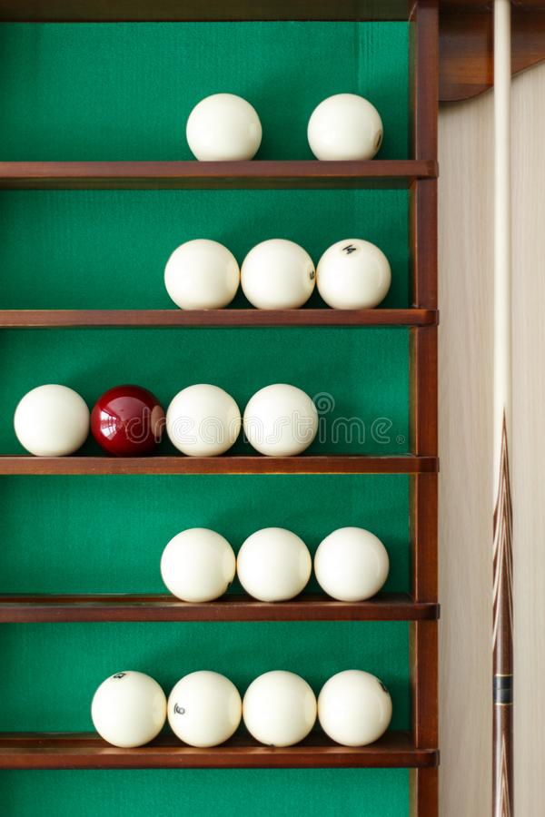 White billiard balls and cue ball for Russian billiards on the shelf. Green cloth. Wooden cue royalty free stock photography