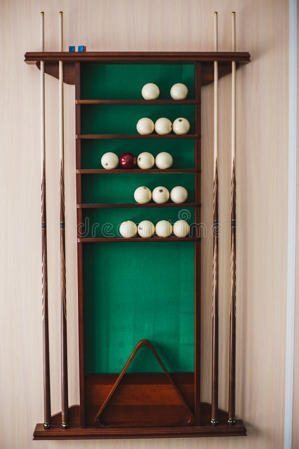 White billiard balls and cue ball for Russian billiards on the shelf. Green cloth. Wooden cue royalty free stock photo