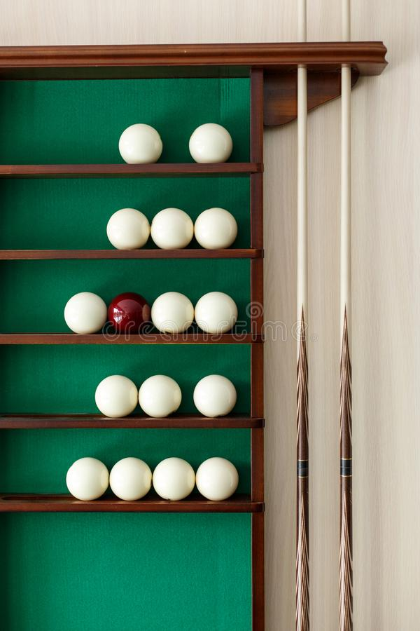 White billiard balls and cue ball for Russian billiards on the shelf. Green cloth. Wooden cue stock images