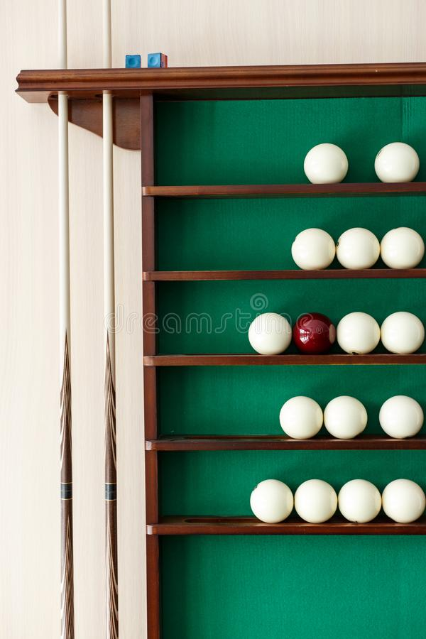 White billiard balls and cue ball for Russian billiards on the shelf. Green cloth. Wooden cue royalty free stock images