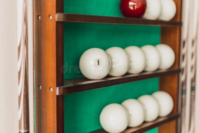White billiard balls and cue ball for Russian billiards on the shelf. Green cloth. Wooden cue royalty free stock image