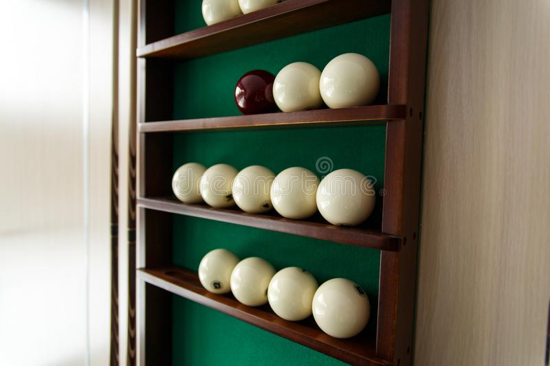 White billiard balls and cue ball for Russian billiards on the shelf. Green cloth. Wooden cue stock photos