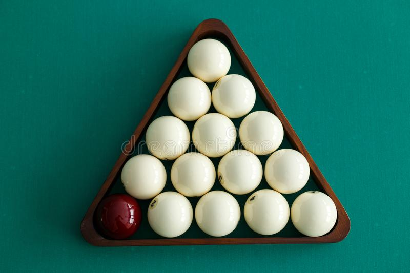 White billiard balls and cue ball for Russian billiards, in a triangle on the table. Top view stock photography
