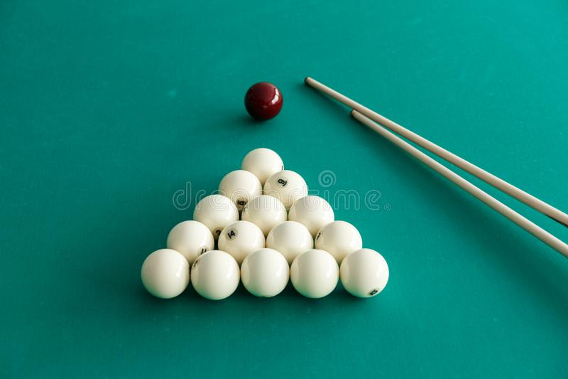 White billiard balls for Russian billiards, in a triangle and cue sticks on the table. Green background stock image