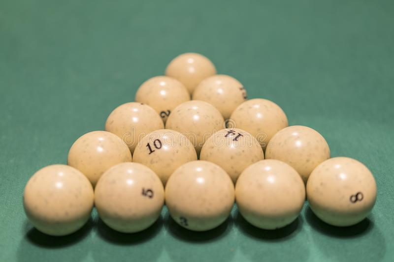 White billiard balls for Russian billiards, in a triangle on the table. Russian billiards balls and cue on the table, the pyramid.  royalty free stock images
