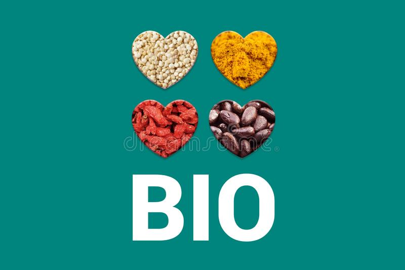 White Bio text on turquoise background and Hearts with cacao nibs, white quinoa grains, dried goji berries and royalty free stock photos