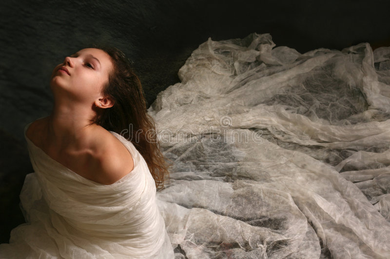White bird. The little girl wrapped up in a fabric royalty free stock images
