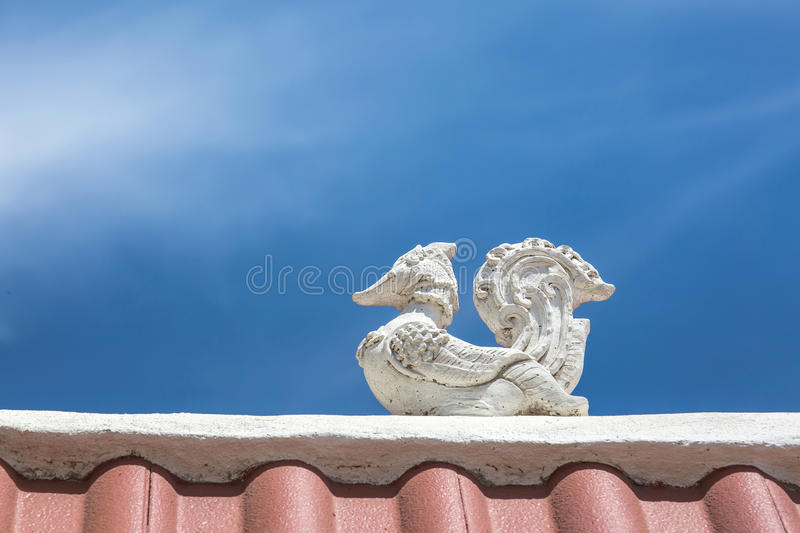 White bird lai thai statue stay on the roof of public location lampoon thailand temple with beautiful blue sky background. In thailand stock photo