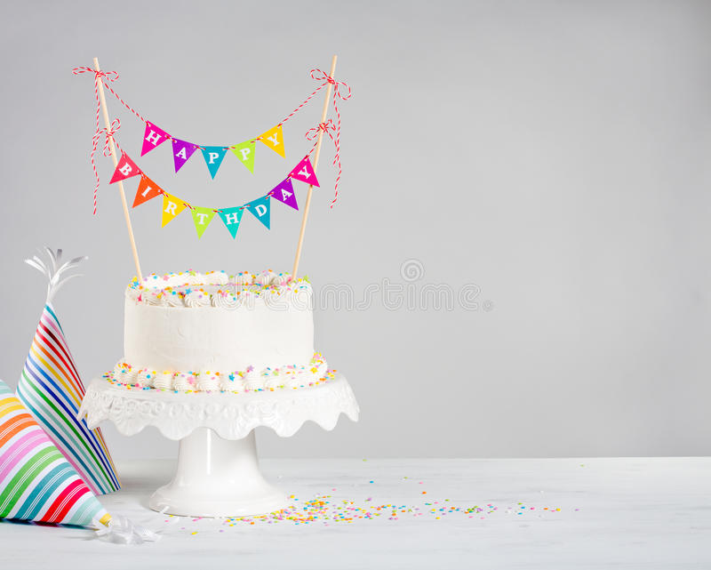 White Birthday Cake colorful bunting. White Buttercream birthday cake with colorful bunting and party hats over white background stock photo