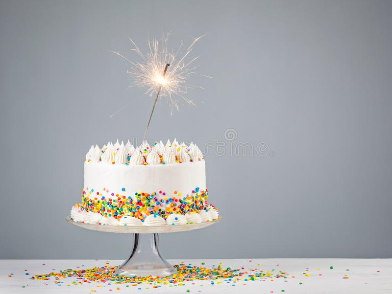 White Birthday Cake with Sparkler. White Birthday cake with colorful Sprinkles and sparkler over a neutral background royalty free stock image
