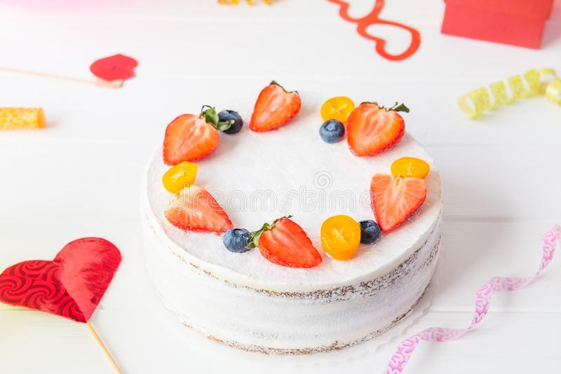 White birthday party background with healthy yougurt berry cake, bright party tools and decoration. Happy holiday design concept. Selective fous, copy space stock photography