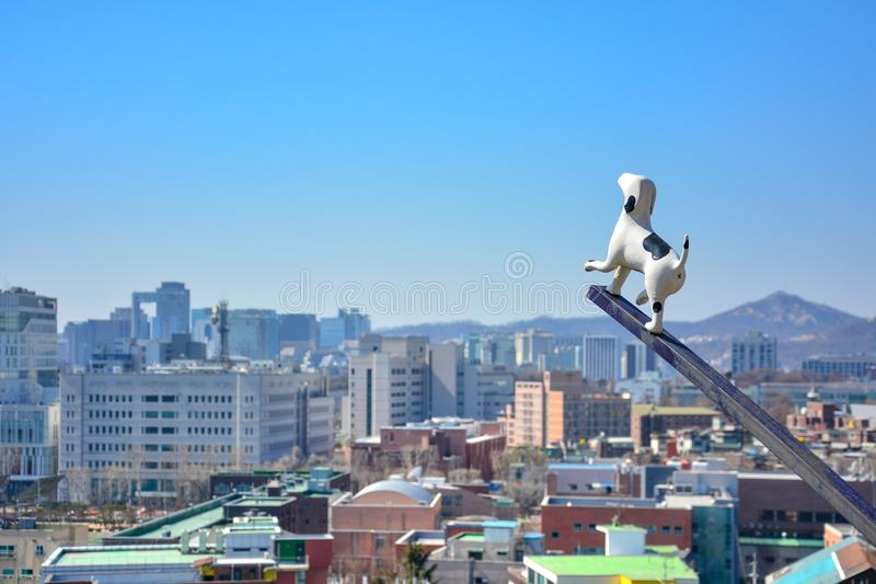 White and black dog statue in Seoul public park, South Korea with blue sky and cityscape background, copy space royalty free stock image