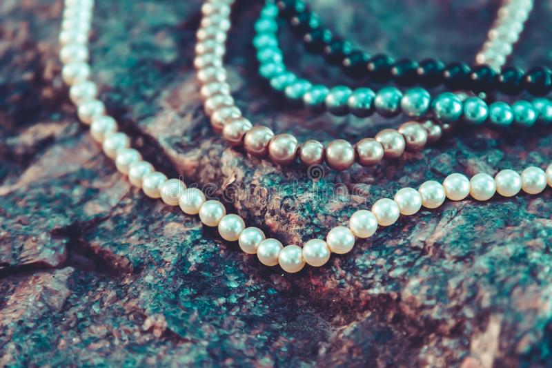 White, black, grey and cream pearls on nature stone background stock photography
