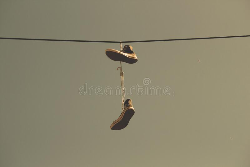 White Black High Top Shoes Hanging on Electric Line royalty free stock image