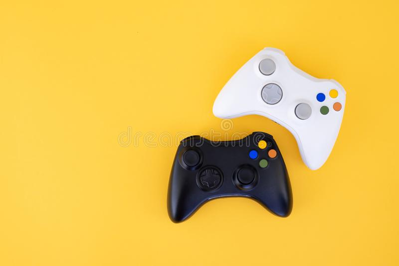 White and black joystick on a yellow background. Gamer concept. Controller for video games stock image