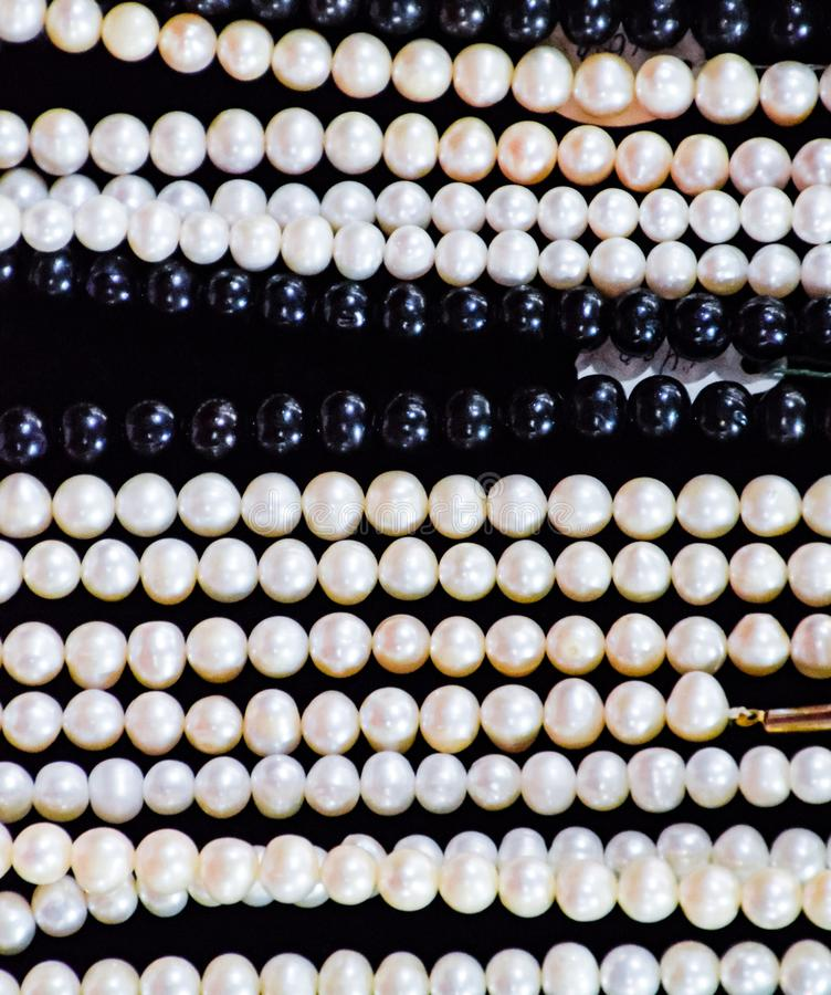 White and black pearls on a black stock photos
