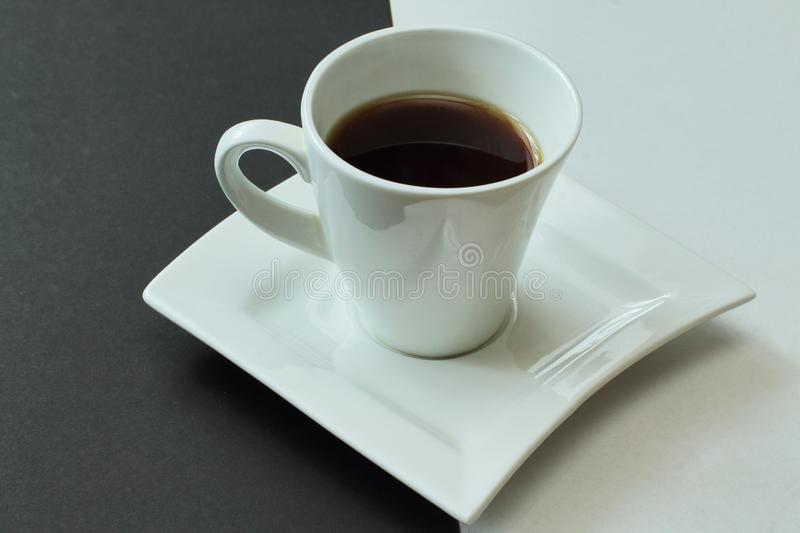 White and black. White porcelain cup with fragrant hot coffee on figured exclusive porcelain saucer. Contrast background stock images