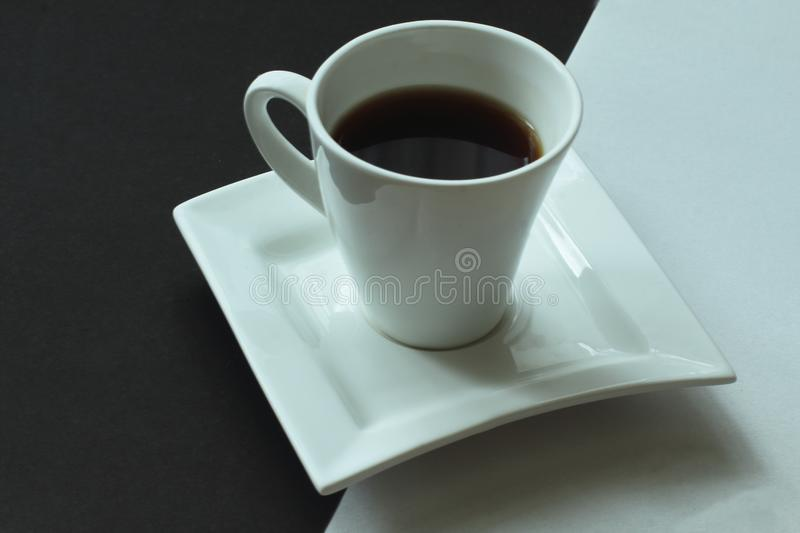 White and black. White porcelain exclusive cup with strong aromatic coffee on saucer of original form on contrasting background. stock images