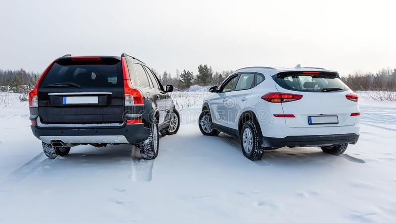 White and black suv car parked in a snowy field. Rear view royalty free stock photography