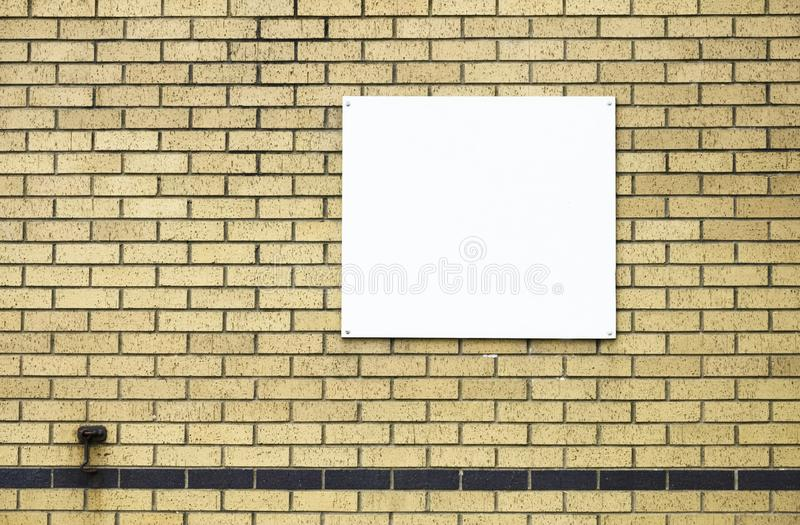 White blank banner poster for advertisement on brick yellow wall. Uk royalty free stock photos