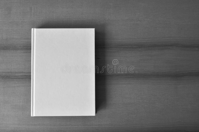 White blank book cover from above. White agenda cover from above. Directly above shot of a white blank book cover on wooden table. Black and white photo. Copy stock image
