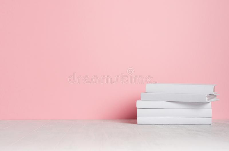 White blank books on white shelf and soft pink wall as modern, elegant home decor. White blank books on white shelf and soft pink wall as modern, elegant home stock photography
