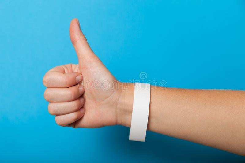 White blank bracelet on hand. Music festival branding wristband, adhesive paper accessory. For concert, event. mockup stock photography