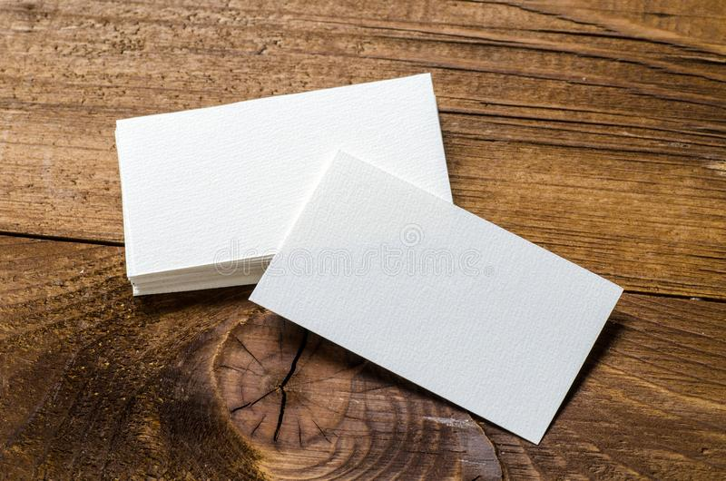 White blank business card. On a wooden background royalty free stock image