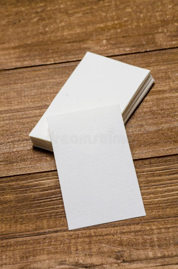 White blank business card. On a wooden background stock photo