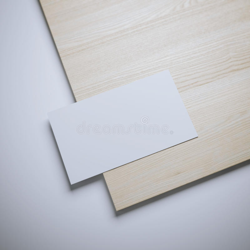 White blank business card and wooden board. On white floor stock photography