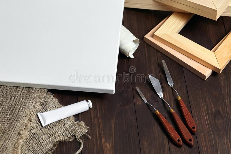 A white blank canvas on stretcher, palette knives, subframes, a tube with oil or acrylic paint and sackcloth stock images