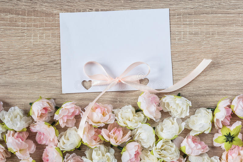 White blank card with a ribbon on a a wooden background with pretty roses. stock photography