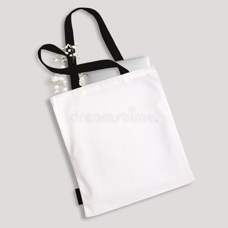 White blank cotton eco tote bag with black straps and little label, laptop and flowers inside. Design mockup stock image