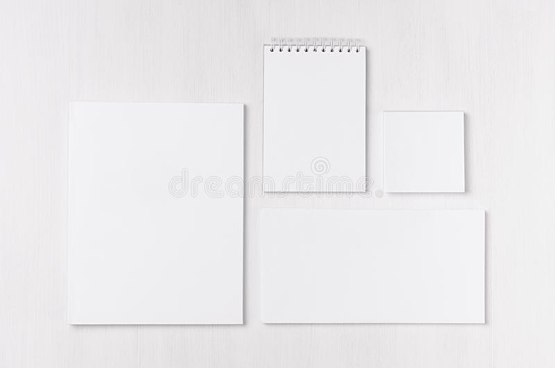 White blank envelope, letterhead, notepad, stickers on soft white wood board. Mock up for branding, business presentations and por royalty free stock images