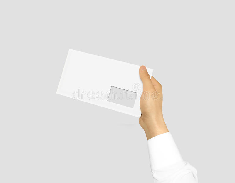 White blank envelope mock up holding in hand. Empty post documen. T design mockup. Clear email display presentation. Postcard template ready for your logo royalty free stock photography