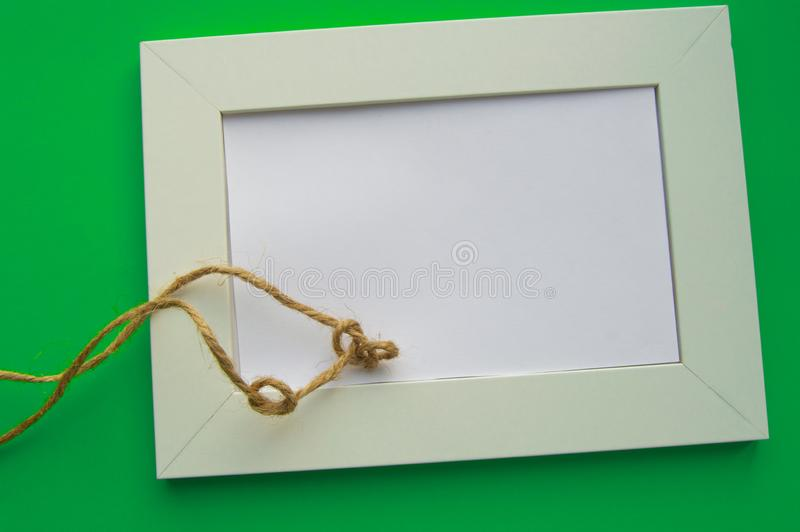 White blank frame with space for text lies on a green background, decorated with twine in knots, celebrating St. Patrick`s Day stock photography