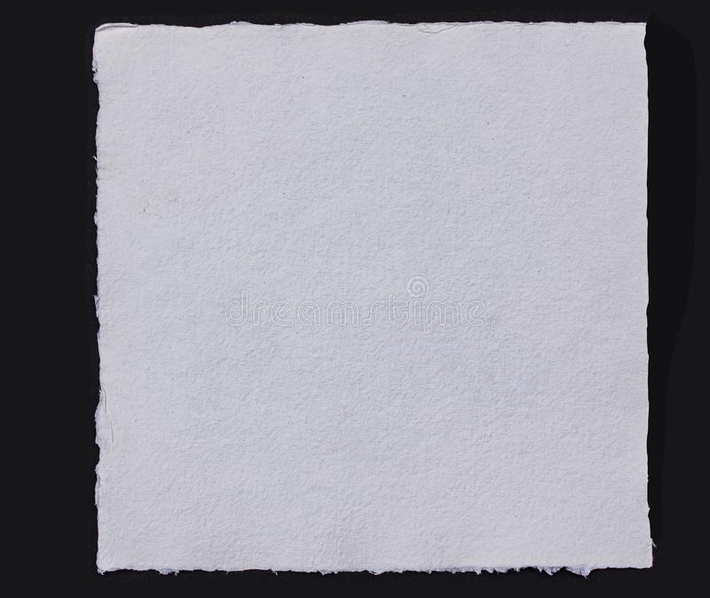 White blank handmade rough watercolor or aquarell paper sheet with torn edges. Close up isolated on black background. Image royalty free stock photo
