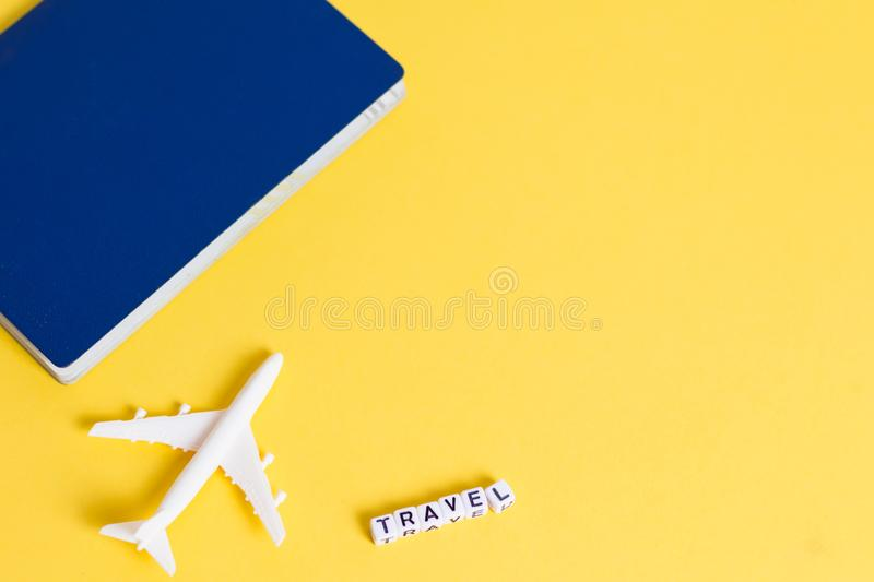 White blank model of passenger plane, passport and word TRAVEL on yellow background. Copy space.  stock images