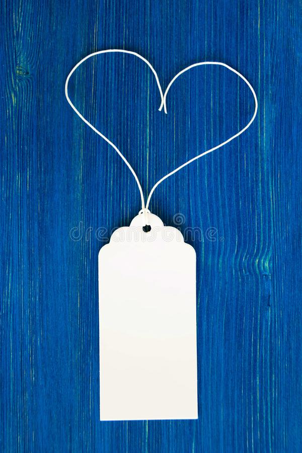 Blank paper price tag or label on the blue wooden background, closeup. stock image