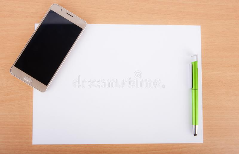 White blank paper sheet with a pen and a smartphone on a wooden royalty free stock images