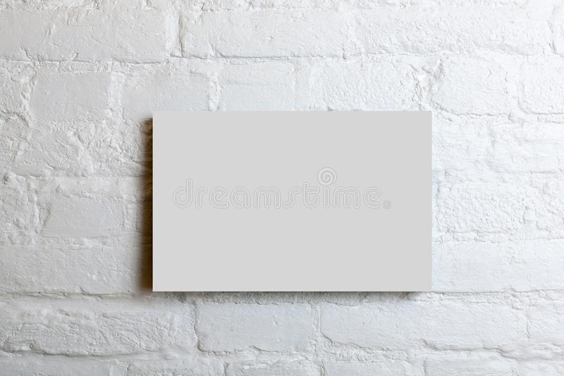 White blank poster in a white brick wall. Template Mock up for your content royalty free stock photography