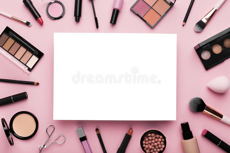 White blank sheet of paper surrounded by luxury decorative cosmetics stock images