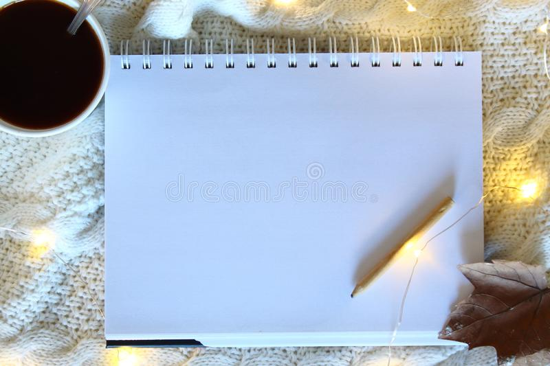White blank sheet of paper on a wooden table. Blank Note Book With Wood Pencil on bed Background. stock photos