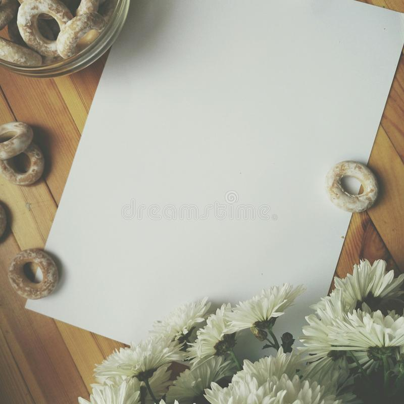 White blank sheet of paper for writing, white flowers and barel on wooden table stock photo