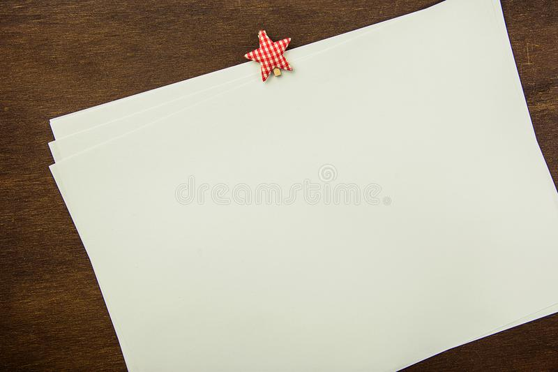 White Blank Sheets of Paper with Star Shape Clipper on Brown Wood Background. New Year`s Resolutions Plans. Letter to Santa Clause. Christmas Party Invitation stock image