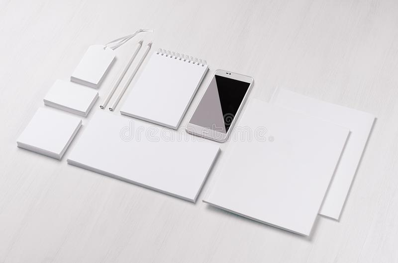 White blank stationery - label, notepad, letterhead, envelop, phone on soft white wooden plank. stock photos