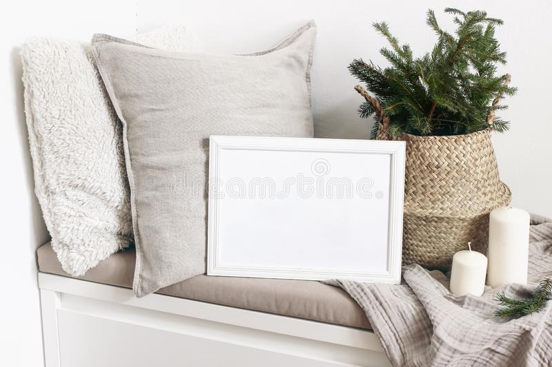 White blank wooden frame mockup with Christmas tree, candles, linen cushions and plaid on the white bench. Poster. Product design. Scandinavian home decor royalty free stock images