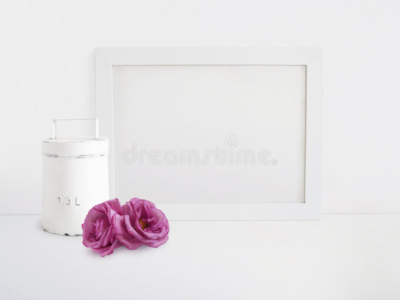 White blank wooden frame mockup with old tin and pink rose flowers lying on the table. Poster product design. Styled stock image
