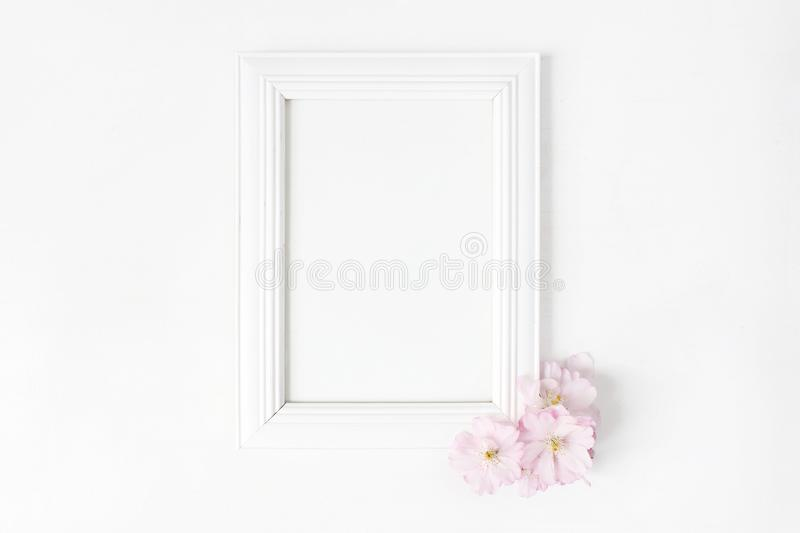White blank wooden picture frame mockup with pink Japanese cherry blossoms lying on the white table. Poster product royalty free stock image