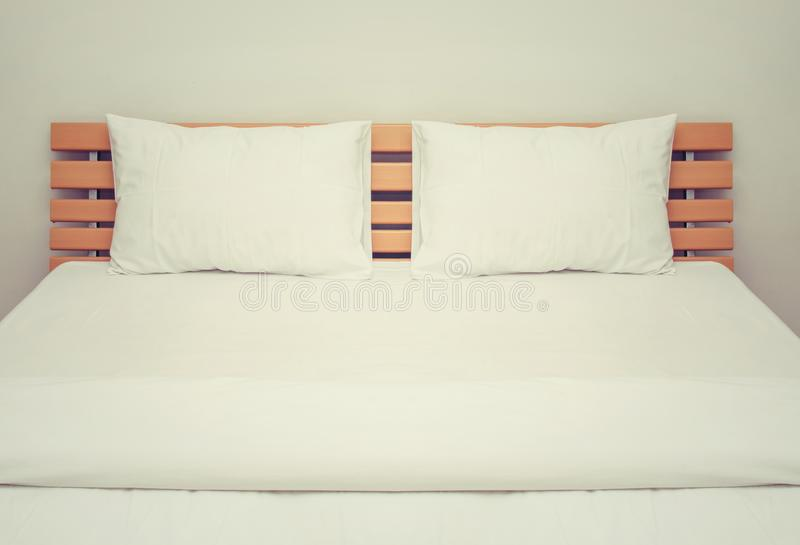 White blankets and pillows on the wood bed in bedroom. Background stock image